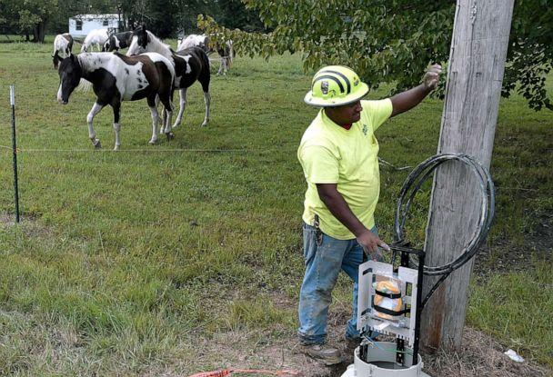 PHOTO: Horses gaze in a field as a utility worker helps install equipment for high speed internet cable in the rural Pocahontas area in Northern Coffee County, Tenn., on Aug. 22, 2018. (The Tennessean via USA Today Network, FILE)