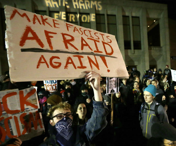 "FILE - In this Jan. 20, 2017 photo, a protester holds a sign that reads ""Make Fascists Afraid Again!"" during a demonstration in front of Kane Hall on the University of Washington campus where far-right commentator Milo Yiannopoulos was giving a speech in Seattle. Prosecutors charged a couple Monday, April 24, 2017 in connection with a shooting earlier in the evening during the protest. (AP Photo/Ted S. Warren, file)"