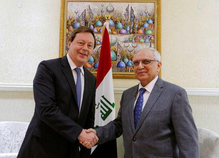 Razzak al-Essa shakes hands with Baker at the Ministry of Finance in Baghdad