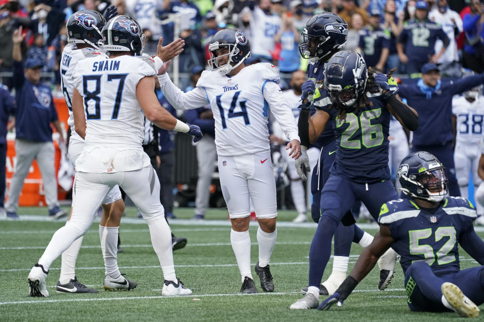 Tennessee Titans kicker Randy Bullock (14) celebrates with tight end Geoff Swaim (87) as Seattle Seahawks defensive back Ryan Neal (26) reacts after Bullock kicked a field goal in overtime to give the Titans a 33-30 win in an NFL football game, Sunday, Sept. 19, 2021, in Seattle. (AP Photo/Elaine Thompson)
