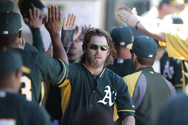 Oakland Athletics' Josh Reddick, center, is greeted by teammates after scoring off a single hit by Oakland Athletics' Derek Norris during the third inning of a spring training baseball game Monday, March 3, 2014, in Phoenix. (AP Photo/Gregory Bull)