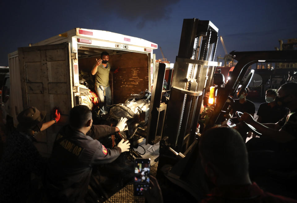 Workers use a forklift to load pieces of wreckage of Sriwijaya Air flight SJ-182 that crashed into the Java Sea on Jan. 9, onto a truck be transported for further investigation, at Tanjung Priok Port in Jakarta, Indonesia, Thursday, Jan. 21, 2021. Indonesian authorities on Thursday ended the search for the wreckage of the plane that nose-dived into the sea, killing all of its passengers on board. (AP Photo/Dita Alangkara)