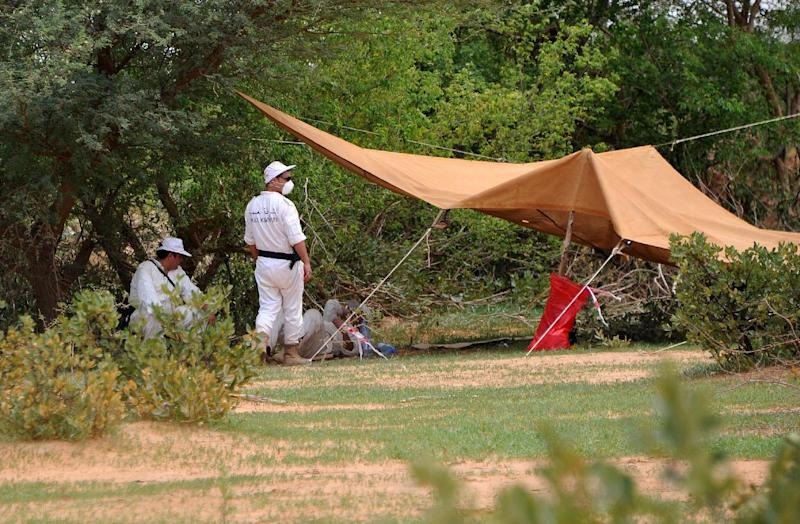Forensics officers stand by a tent set up at the crash site of the Air Algerie flight AH5017 in northern Mali on July 29, 2014 (AFP Photo/Sia Kambou)