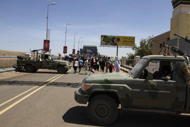 "Demonstrators walk past army vehicles protecting the entrance to a rally near the military headquarters in Khartoum, Sudan, Monday, April 15, 2019. The Sudanese protest movement on Monday welcomed the ""positive steps"" taken by the ruling military council, which held talks over the weekend with the opposition leaders and released some political prisoners. The praise came despite a brief incident earlier Monday where activists said soldiers attempted to disperse the ongoing protest sit-in outside the military headquarters in the capital, Khartoum, but eventually backed off. (AP Photo/Salih Basheer)"