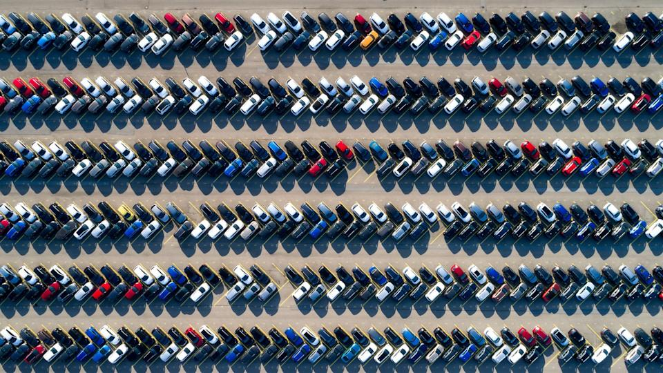 Aerial view of new cars of different brands parked in rows on a lot.