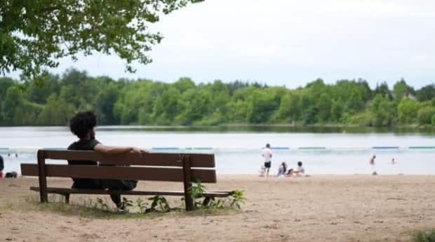 Someone sits on a bench at Mooney's Bay beach along the Rideau River on June 11. (Félix Desroches/Radio-Canada - image credit)