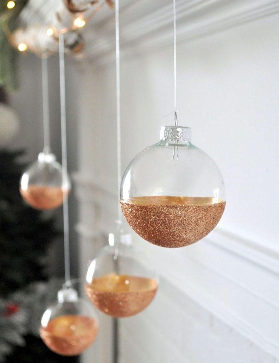 """<p>Copper paint and glitter lend an air of rustic elegance to these beautiful ornaments. </p><p><strong>Get the tutorial at <a href=""""https://jenniferrizzo.com/2016/11/modern-rustic-mantel-easy-diy-glitter-ornaments.html"""" rel=""""nofollow noopener"""" target=""""_blank"""" data-ylk=""""slk:Jennifer Rizzo"""" class=""""link rapid-noclick-resp"""">Jennifer Rizzo</a>.</strong></p><p><a class=""""link rapid-noclick-resp"""" href=""""https://www.amazon.com/Martha-Stewart-Crafts-Multi-Surface-Metallic/dp/B007C7X8QW?tag=syn-yahoo-20&ascsubtag=%5Bartid%7C10050.g.28831556%5Bsrc%7Cyahoo-us"""" rel=""""nofollow noopener"""" target=""""_blank"""" data-ylk=""""slk:SHOP COPPER CRAFT PAINT"""">SHOP COPPER CRAFT PAINT</a></p>"""