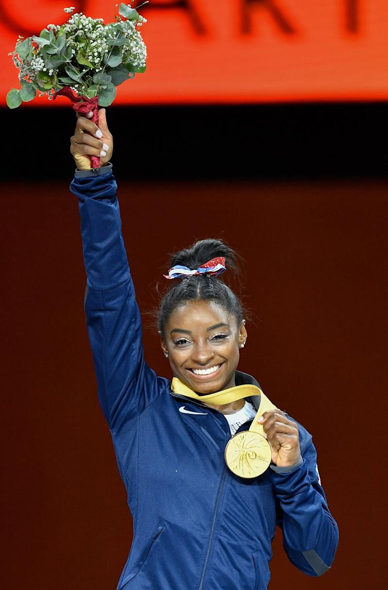 USA's Simone Biles poses on the podium during the medals ceremony of the womens all-around final at the FIG Artistic Gymnastics World Championships at the Hanns-Martin-Schleyer-Halle in Stuttgart, southern Germany, on October 10, 2019. - USA's Simone Biles won Gold ahead of China's Tang Xijing (Silver) and Russia's Angelina Melnikova (Bronze). (Photo by Thomas KIENZLE / AFP) (Photo by THOMAS KIENZLE/AFP via Getty Images)