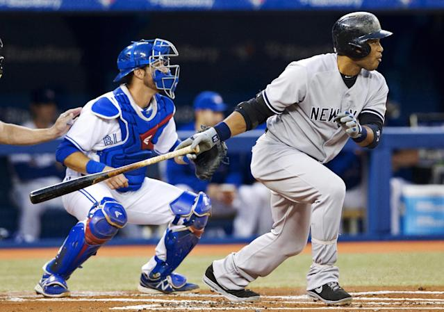 New York Yankees' Robinson Cano follows through on a base hit in front of Toronto Blue Jays catcher J.P. Arencibia, right, during the first inning of MLB American League baseball action in Toronto Wednesday, Sept. 18, 2013. (AP Photo/The Canadian Press, Mark Blinch)