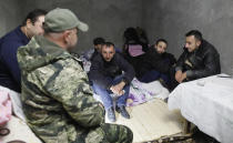 Men sit in a bomb shelter during shelling by Azerbaijan's artillery during a military conflict in Stepanakert, the separatist region of Nagorno-Karabakh, Friday, Oct. 23, 2020. Heavy fighting raged Friday over Nagorno-Karabakh even as top diplomats from Armenia and Azerbaijan visited Washington for negotiations on settling the neighboring countries' decades-long conflict. (AP Photo)