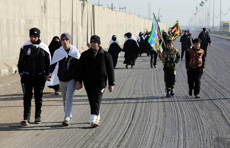 Shiite faithful pilgrims march to Karbala for Arbaeen in Baghdad, Iraq, Tuesday, Dec. 17, 2013. The holiday marks the end of the forty day mourning period after the anniversary of the 7th century martyrdom of Imam Hussein the Prophet Muhammad's grandson. (AP Photo/Karim Kadim)