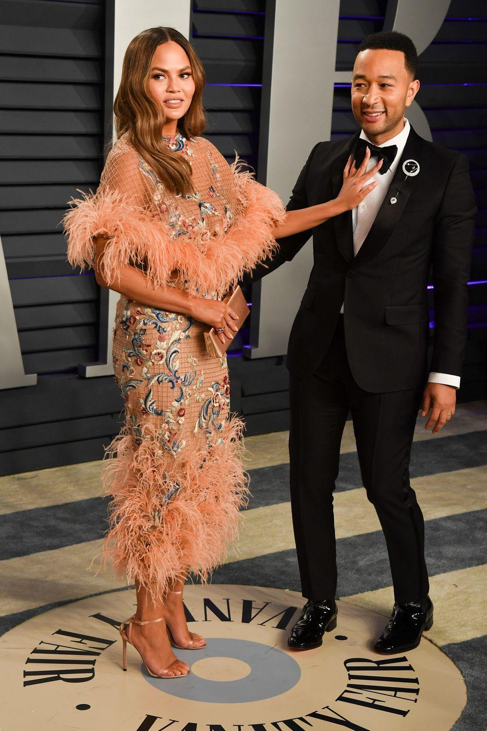 <p>Teigen playfully pushes Legend away while posing on the red carpet at the 2019 Oscars afterparty.</p>