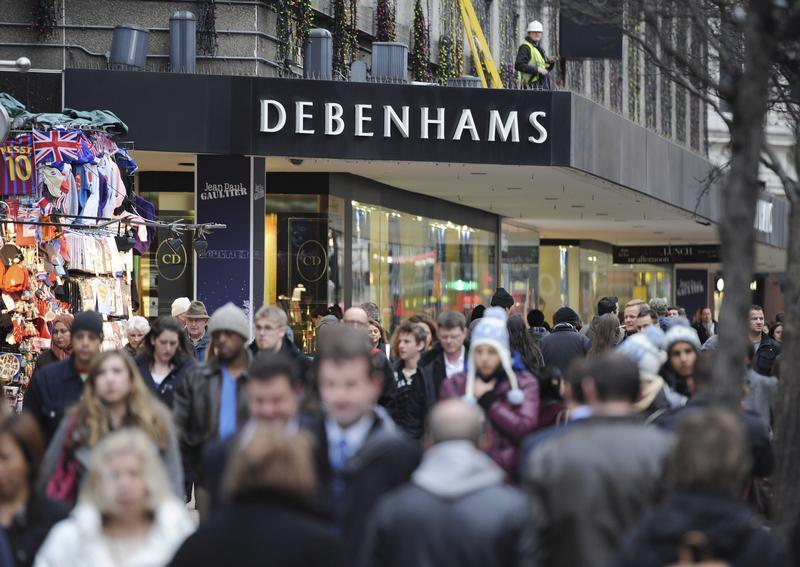People walk past Debenhams department store on Oxford Street, in central London