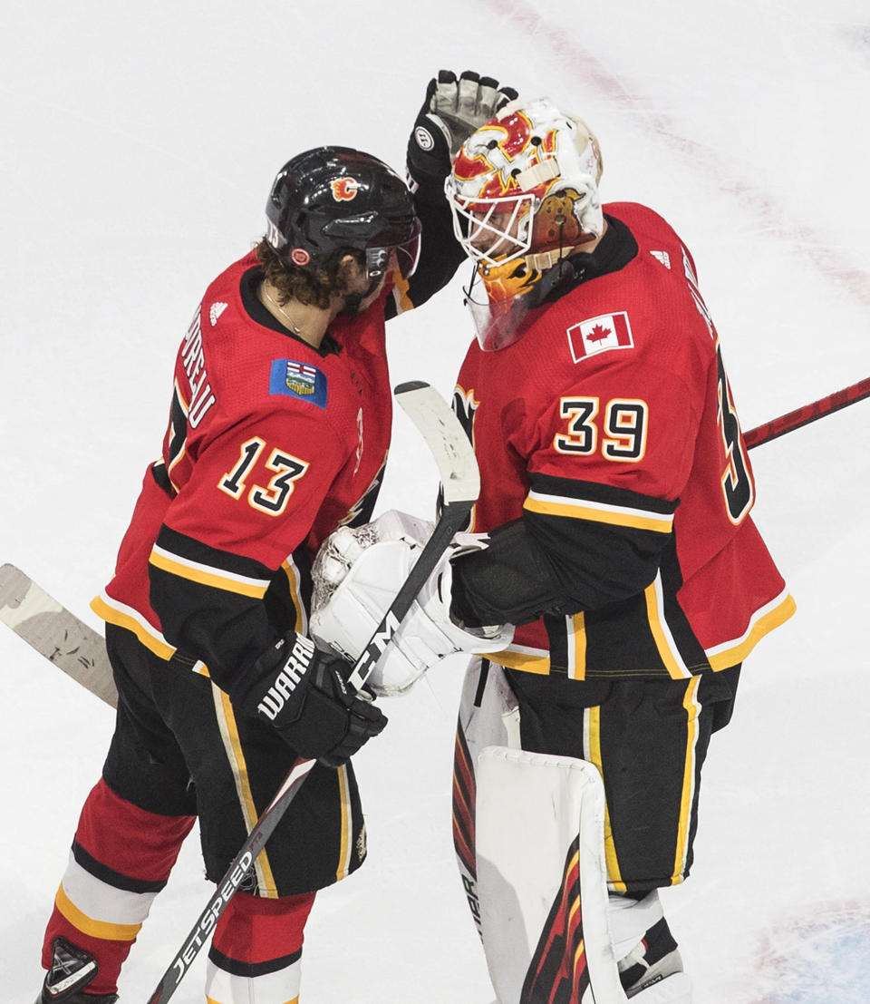 Calgary Flames' Johnny Gaudreau (13) and goalie Cam Talbot (39) celebrate the win over the Dallas Stars during the first round of an NHL Stanley Cup playoff hockey series, Friday, Aug. 14, 2020, in Edmonton, Alberta. (Jason Franson/The Canadian Press via AP)