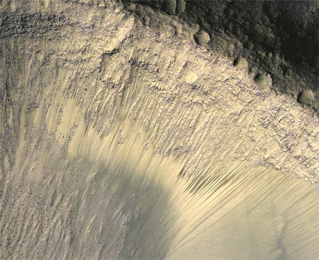 "This animated image series from the HiRISE camera on NASA's Mars Reconnaissance Orbiter show dark markings on a Martian slope changing with the seasons. <p class=""copyright"">NASA/JPL-Caltech/Univ. of Arizona</p>"