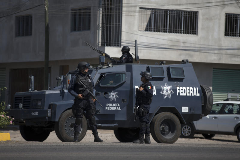 Federal police patrol the entrance to Apatzingan, Mexico, Tuesday, Jan. 14, 2014. Mexican soldiers and federal police kept a tense standoff with vigilantes Tuesday after a new government campaign to stop violence in the western Michoacan state turned deadly. A clash occurred as the government sent more troops to where the vigilantes have been fighting the Knights Templar cartel. Federal and state officials met late Tuesday with leaders of vigilante groups but failed to reach a disarmament agreement. (AP Photo/Eduardo Verdugo)