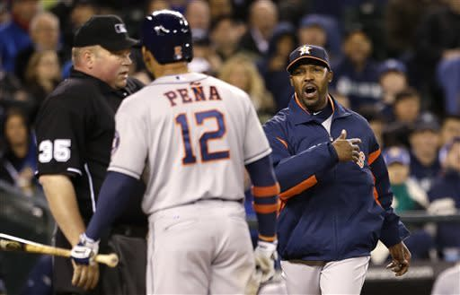 Houston Astros manager Bo Porter, right, runs toward home to bring Carlos Pena back to the dugout as Pena argues with plate umpire Wally Bell after being called out on strikes against the Seattle Mariners in the fifth inning of a baseball game Wednesday, April 10, 2013, in Seattle. (AP Photo/Elaine Thompson)