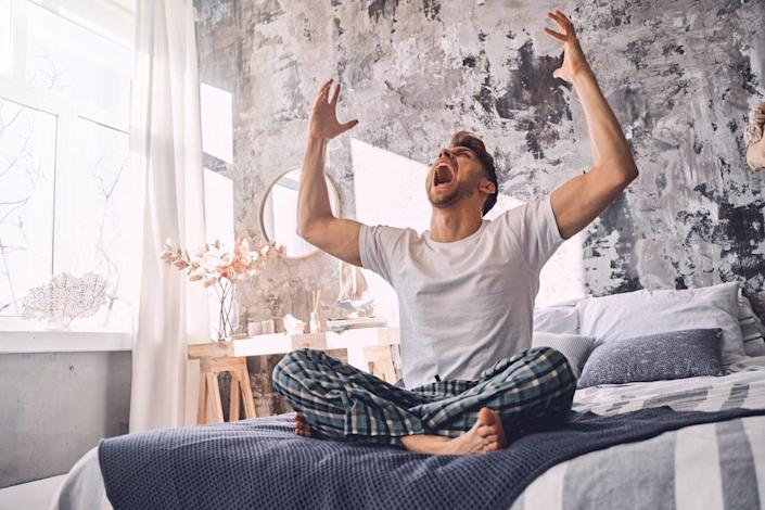 Irritated man crossing legs while sitting on the bed and shouting at home