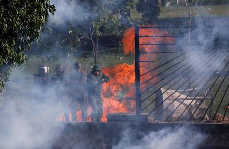 Riot security forces look through an air base fence destroyed by demonstrators rallying against Venezuela's President Nicolas Maduro in Caracas, Venezuela, May 31, 2017. REUTERS/Carlos Garcia Rawlins