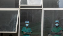 Medical staff look out from a window as officials prepare for a ceremony to commence the country's first coronavirus vaccinations using AstraZeneca COVID-19 vaccine manufactured by the Serum Institute of India and provided through the global COVAX initiative, at Kenyatta National Hospital in Nairobi, Kenya Friday, March 5, 2021. Urgent calls for COVID-19 vaccine fairness rang through African countries on Friday as more welcomed or rolled out doses from the global COVAX initiative, with officials acutely aware their continent needs much more. (AP Photo/Ben Curtis)