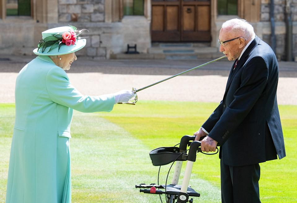WINDSOR, ENGLAND - JULY 17: Queen Elizabeth II (using the sword that belonged to her father, King George VI) confers the Honour of Knighthood on Captain Sir Thomas Moore before presenting him with the insignia of Knight Bachelor during an investiture ceremony at Windsor Castle on July 17, 2020 in Windsor, England.  British World War II veteran Captain Tom Moore raised over £32 million for the NHS during the coronavirus pandemic.  (Photo by Pool/Samir Hussein/WireImage)