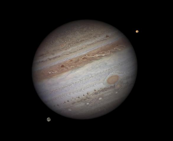 Winner (Solar System) and Overall Winner 'Jupiter with Io and Ganymede' by Damian Peach (UK) Jupiter depicted along with two of its 64 known moons, Io and Ganymede, showing the surface of the gas giant streaked with colourful bands and dotted with huge oval storms; detail is also visible on the two moons. The photos which make up this composite image were taken from Barbados where the excellent atmospheric clarity allows for exceptionally clear astronomical pictures.
