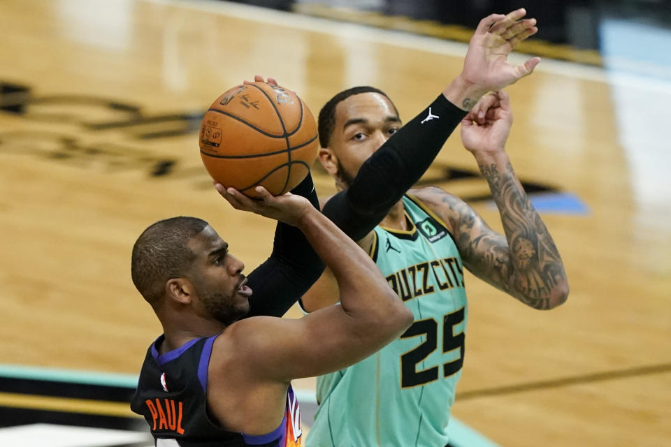 Phoenix Suns guard Chris Paul scores past Charlotte Hornets forward P.J. Washington during the second half of an NBA basketball game on Sunday, March 28, 2021, in Charlotte, N.C. (AP Photo/Chris Carlson)