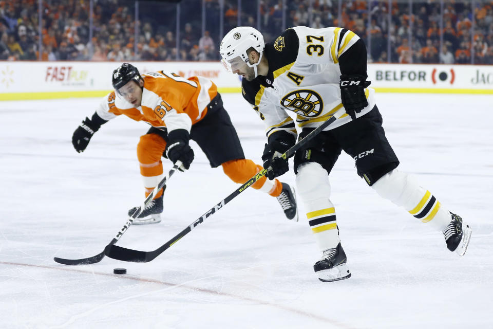 Boston Bruins' Patrice Bergeron (37) tries to skate past Philadelphia Flyers' Justin Braun (61) during the first period of an NHL hockey game, Tuesday, March 10, 2020, in Philadelphia. (AP Photo/Matt Slocum)