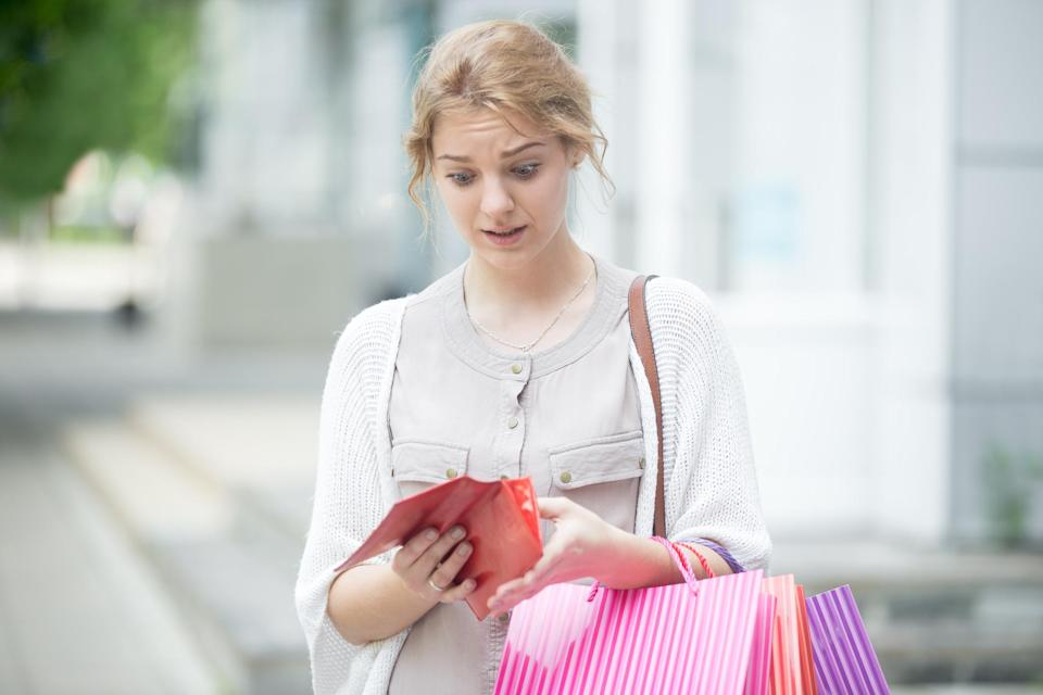 young woman carrying shopping bags and looking into wallet with concern