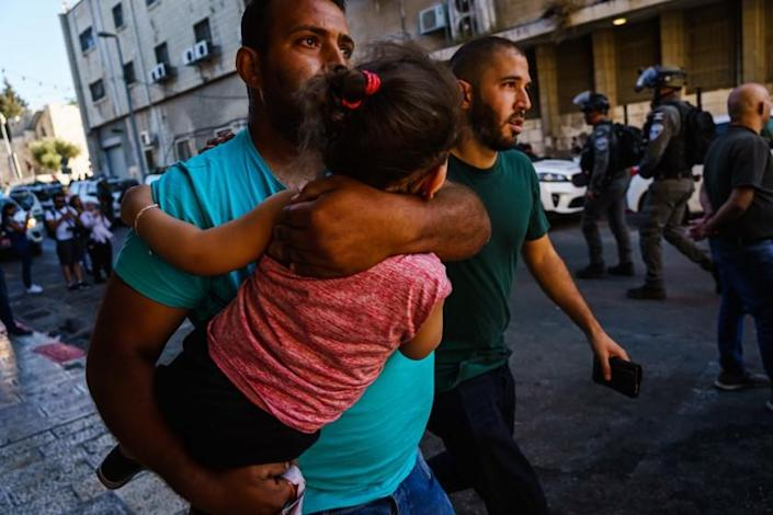 JERUSALEM, ISRAEL -- JUNE 6, 2021: A man carries a child away from the chaos of a panicked crowd as Israeli security forces throw stun grenades to disperse a growing crowd at a news conference calling for the release of Muna al-Kurd and Mohammed al-Kurd, two prominent activists who are residents of the Sheikh Jarrah neighborhood, at a local police station near the Damascus Gate at Old City, in East Jerusalem, Israel, Sunday, June 6, 2021. (MARCUS YAM / LOS ANGELES TIMES)