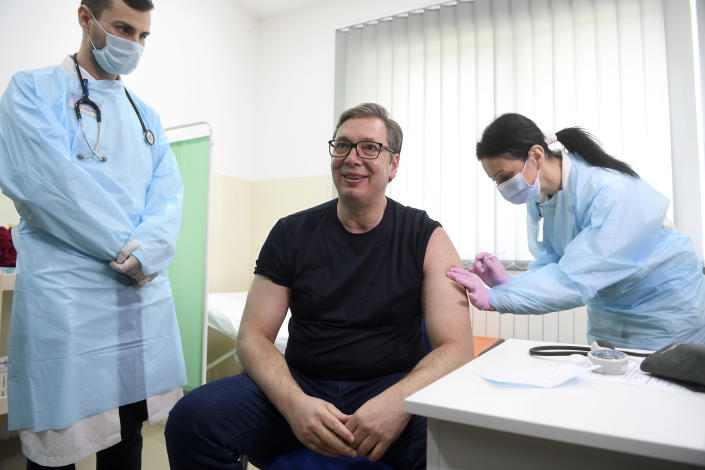 In this photo provided by the Serbian Presidential Press Service, Serbian President Aleksandar Vucic, centre, receives a dose of the Chinese Sinopharm vaccine in the village of Rudna Glava, Serbia, Tuesday, April 6, 2021. Vucic finally rolled up his sleeve for a coronavirus vaccine Tuesday and to encourage his country's increasingly skeptical Serbs to get vaccinated themselves. (Serbian Presidential Press Service via AP)