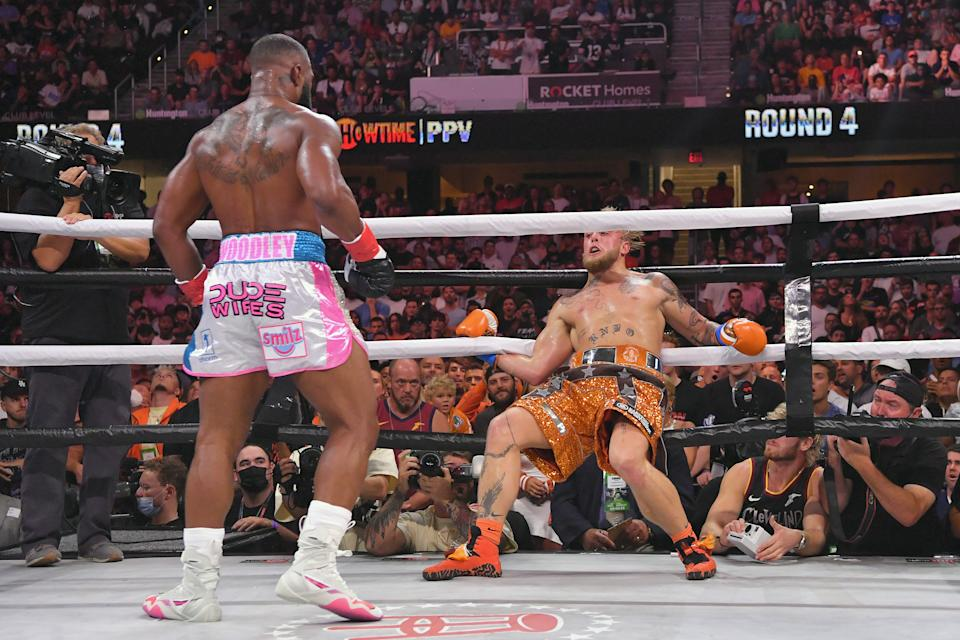 Jake Paul (pictured right) holds onto the ropes after being punched by Tyron Woodley (pictured left) in their cruiserweight bout.