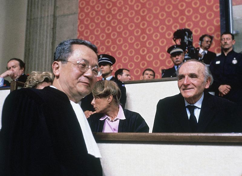 """FILE - In this May, 11, 1987 file photo, 73-year old former Lyon Gestapo chief Klaus Barbie, right, smiles while his lawyer Jacques Verges, left, passes at the beginning of a trial inside the local Palais de Justice in Lyon, France. Verges, called the """"Devil's advocate"""" for his flamboyant courtroom defense of the likes of former Nazi Barbie and Carlos the Jackal, died Thursday, Aug. 15, 2013 of cardiac arrest in Paris. He was 88. (AP Photo/File)"""