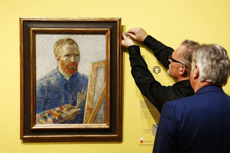 "Curators hang an 1888 self-portrait of Vincent Van Gogh in which he painted himself behind a canvas, brushes and palette in hand, the final painting before the reopening after a seven-month renovation, kicking off with ""Vincent At Work,"" an exhibition that shows Van Gogh's working methods, right down to the paints, brushes and other tools he used, Amsterdam, Netherlands, Wednesday, May 1, 2013. (AP Photo/Vincent Jannink)"