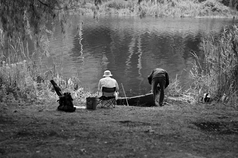 Two people at the edge of a pond fishing.