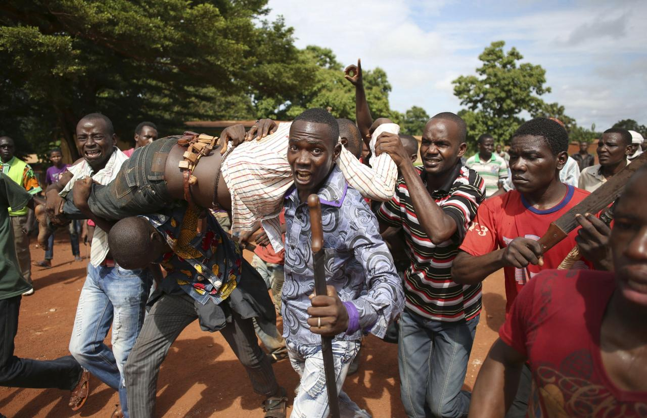 Protesters carry a man who was shot by French soldiers after French troops opened fire at protesters blocking a road in Bambari May 22, 2014. 