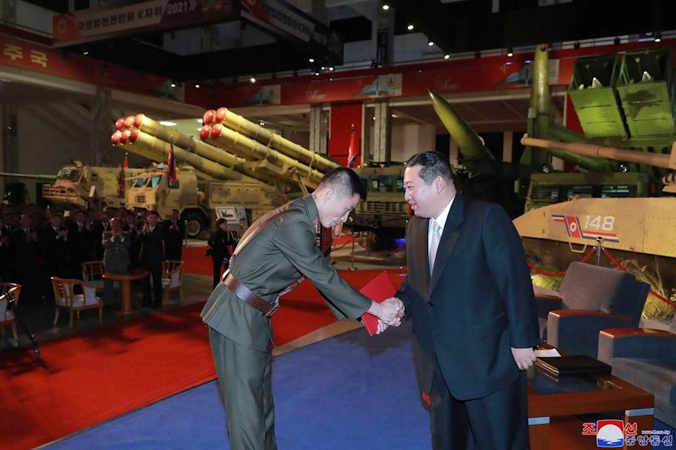 In this photo provided by the North Korean government, Kim Jong Un (right) visits an exhibition of weapons systems in Pyongyang on 11 October. Independent journalists were not given access to cover the event depicted in this image distributed by the North Korean government (AP)