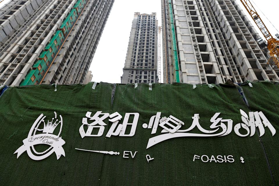 A peeling logo of the Evergrande Oasis, a housing complex developed by Evergrande Group, is pictured outside the construction site where the residential buildings stand unfinished, in Luoyang, China September 16, 2021. Picture taken September 16, 2021. REUTERS/Carlos Garcia Rawlins