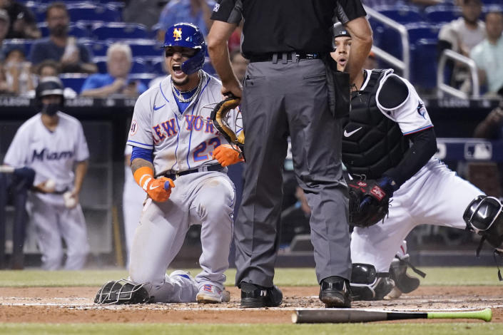 New York Mets' Javier Baez, left, reacts after scoring past Miami Marlins catcher Alex Jackson, right, during the second inning of a baseball game, Wednesday, Aug. 4, 2021, in Miami. (AP Photo/Lynne Sladky)