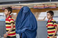 Families evacuated from Kabul, Afghanistan, walk through the terminal to board a bus after arriving at Washington Dulles International Airport, in Chantilly, Va., on Wednesday, Sep. 1, 2021. (AP Photo/Gemunu Amarasinghe)
