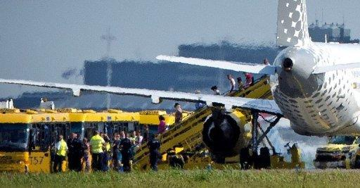 Passengers disembark a plane of Spanish airline Vueling after it landed at Schiphol Airport in Amsterdam