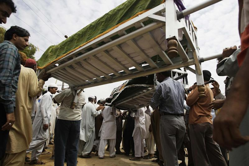 Pakistanis attend the funeral of factory workers in Karachi, Pakistan, Thursday, Sept. 13, 2012. Pakistani police say they have registered a murder case against the owners and managers of a garment factory in the southern city of Karachi where a fire killed hundreds of people. (AP Photo/Fareed Khan)