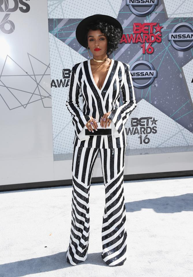 <p>While Janelle Monae only wears black and white, she always manages to wear something cool and different despite her limited color palate. For the 2016 BET Awards, she selected a striped sequin suit from Sass & Bide. She accessorized with a wide-brimmed hat, gold choker, oversized hoop earrings, and purple rings to honor Prince.<i>(Photo: Getty Images)</i></p>