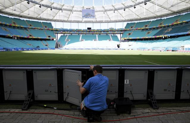 A man works on the electronic advertising boards of the soccer pitch inside the Arena Fonte Nova stadium ahead of the 2014 World Cup in Salvador, June 12, 2014. REUTERS/Marcos Brindicci (BRAZIL - Tags: SOCCER SPORT WORLD CUP)