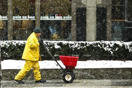 A man throws salt on a street during the arrival of a snowstorm in Exchange Place, New Jersey