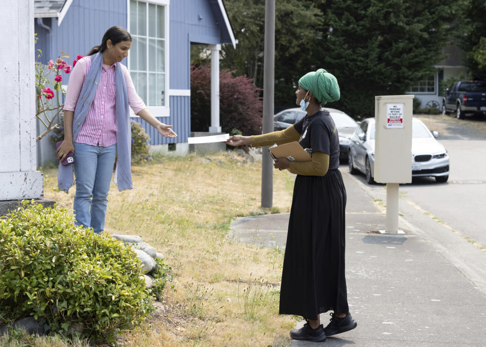 Shukri Olow, right, a Muslim woman who is running for King County Council District 5, hands a campaign flier to Tayyabah Ahmed, left, Saturday, Aug. 14, 2021, as she campaigns in Renton, Wash., south of Seattle. Muslim Americans in their 20s and 30s who grew up amid the aftershocks of the Sept. 11, 2001 terrorist attacks came of age in a world not necessarily attuned to their interests, their happiness and their well-being. Olow says the aftermath of the attacks has helped motivate her to become a community organizer and to run for office in Washington state. (AP Photo/Karen Ducey)