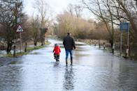 EARITH, UNITED KINGDOM - JANUARY 19: A child cycles along the flooded road by the side of the River Great Ouse after it was closed due to flood waters on January 19, 2021 in Earith, United Kingdom. Storm Christoph is the first named storm of 2021 with heavy rainfall bringing flooding areas of the UK including Cambridgeshire, Greater Manchester and South Yorkshire. (Photo by Leon Neal/Getty Images)