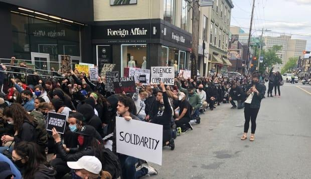Demonstrators took a knee on Spring Garden Road in Halifax last June to protest the death of George Floyd. The unarmed Black man was killed by a Minneapolis police officer last May. (Brian Daly/CBC - image credit)