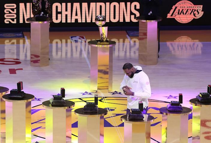 Lakers forward LeBron James puts on his NBA championship ring during a ceremony Dec. 22 at Staples Center.