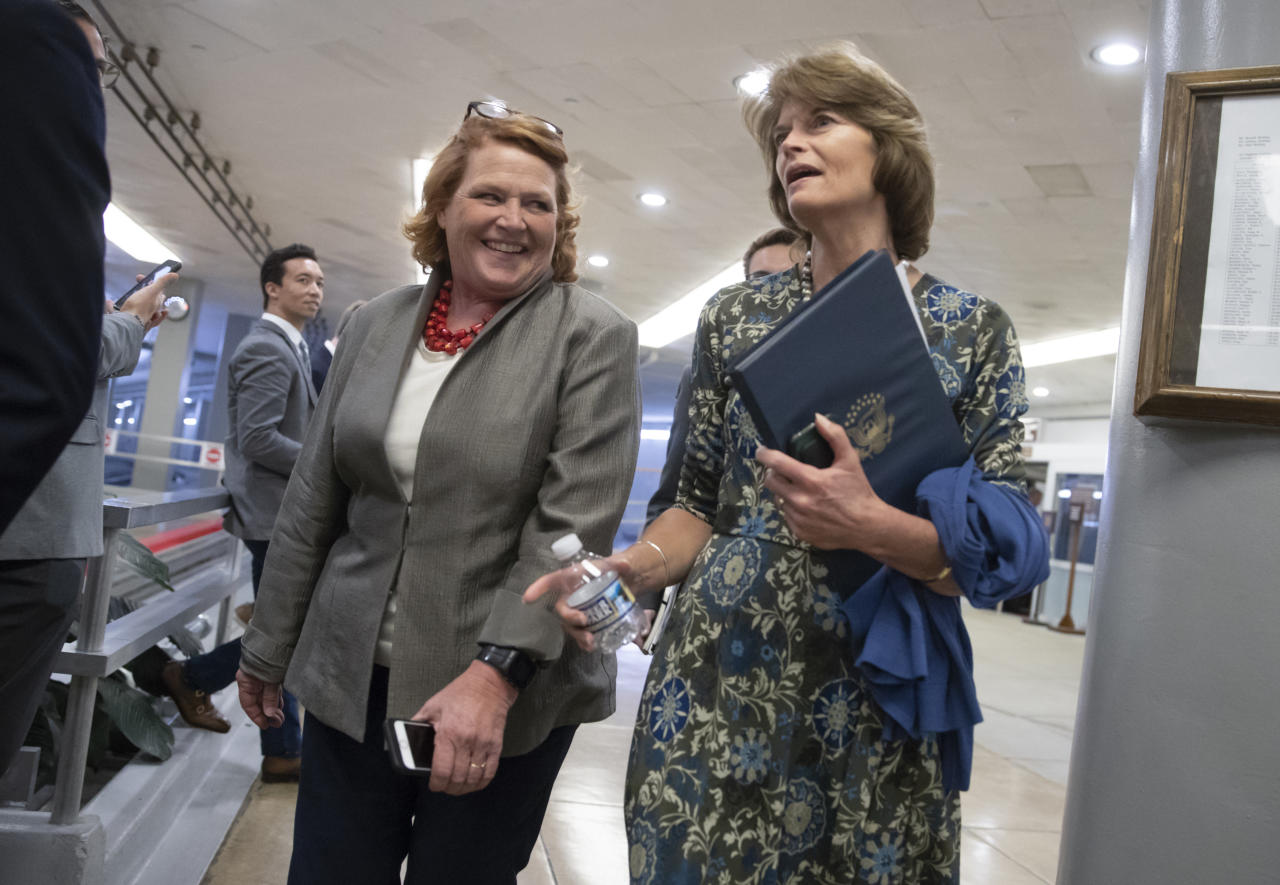 Sen. Heidi Heitkamp, D-N.D., left, and Sen. Lisa Murkowski, R-Alaska, arrive to vote on a bill to expand private care for military veterans as an alternative to the troubled Veterans Affairs health system, on Capitol Hill in Washington, Wednesday, May 23, 2018. (AP Photo/J. Scott Applewhite)
